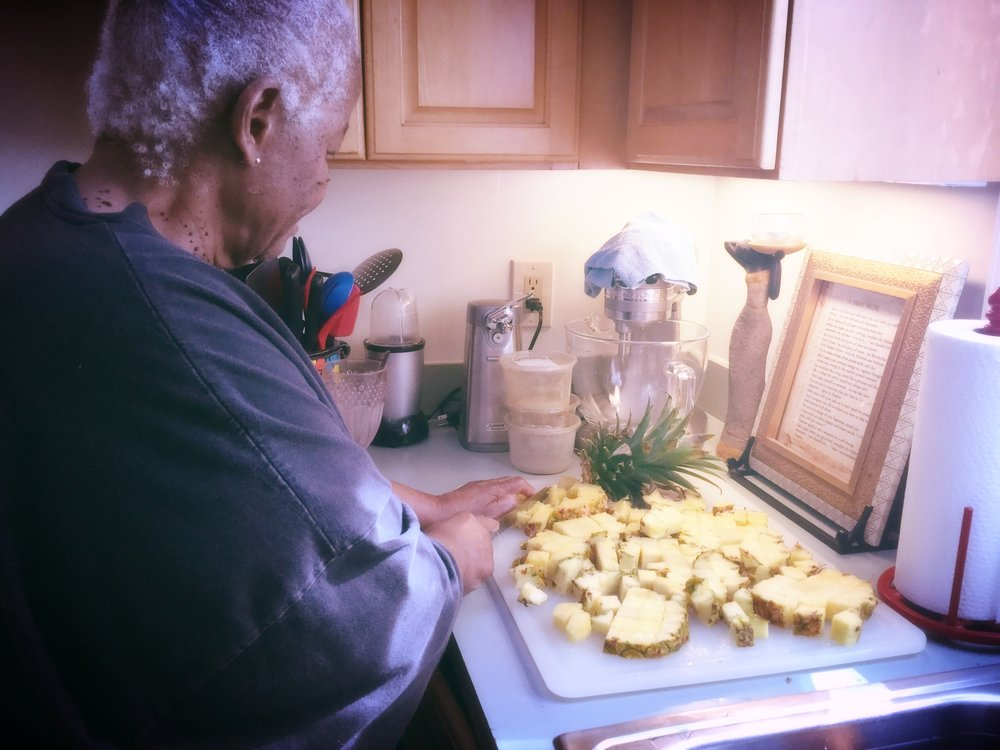 Grannie chops up fresh pineapples, nothing wasted, including the core and thorny outer skin goes into her smoothie