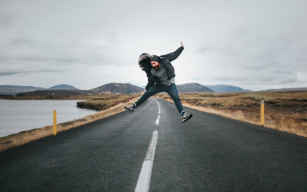 Man jumping on a road in Iceland