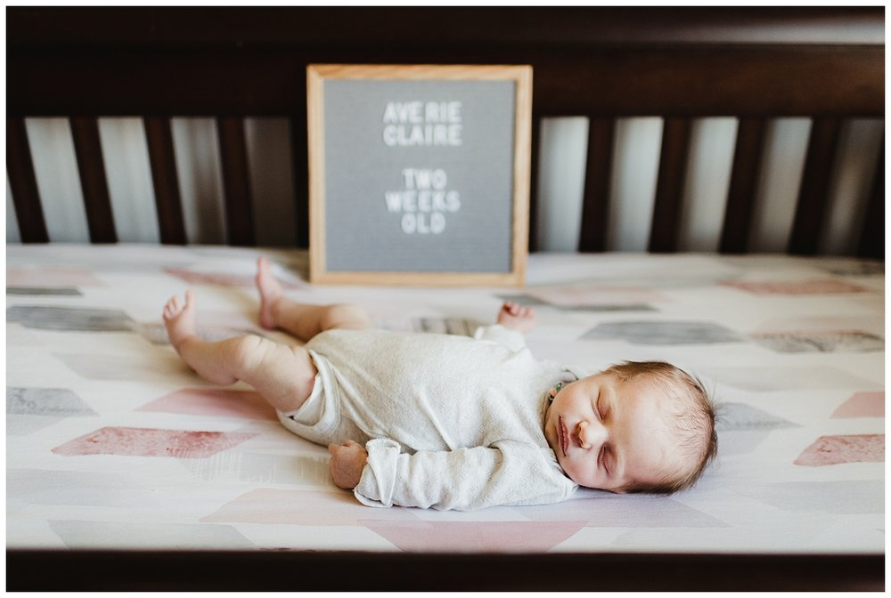 in home lifestyle newborn session madison wi baby in crib with sign.jpg