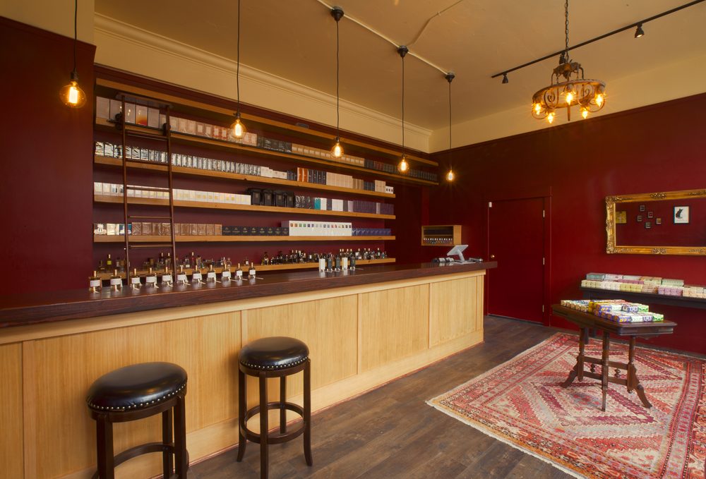 Our Portland Retail Boutique, 3584 SE Division Street The atmosphere of Fumerie Parfumerie evokes the opulence and sumptuousness of a bygone era. The name Fumerie Parfumerie literally translates to opium den perfume boutique, and the intimate, inviting space pays homage to our namesake. The color palette is an array of oxblood red, warm amber and jet black. Rich, dark woods accent every inch of the space from the floor to the exquisite hand-crafted bar. The rustic wood floor is blanketed with opulent Persian rugs. Upon entering Fumerie Parfumerie, one's attention is immediately drawn to the exquisite wooden bar. This serves both as the focal point and the heart of Fumerie Parfumerie. From here, sales associates tend to the customer's every fragrant need. A library ladder allows the staff access to the visually-stunning wall of fragrances located behind the bar. Patrons are invited to take a seat at the bar and indulge in the world's finest fragrances. Our experts are readily available to assist you in choosing the perfect scent.