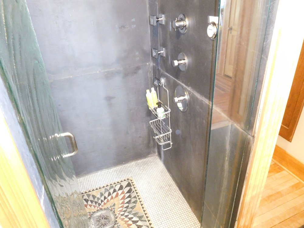 Carriage House downstairs bathroom. Spacious steam shower, mosaic tile floor, slate walls. water jets, pressed glass door.