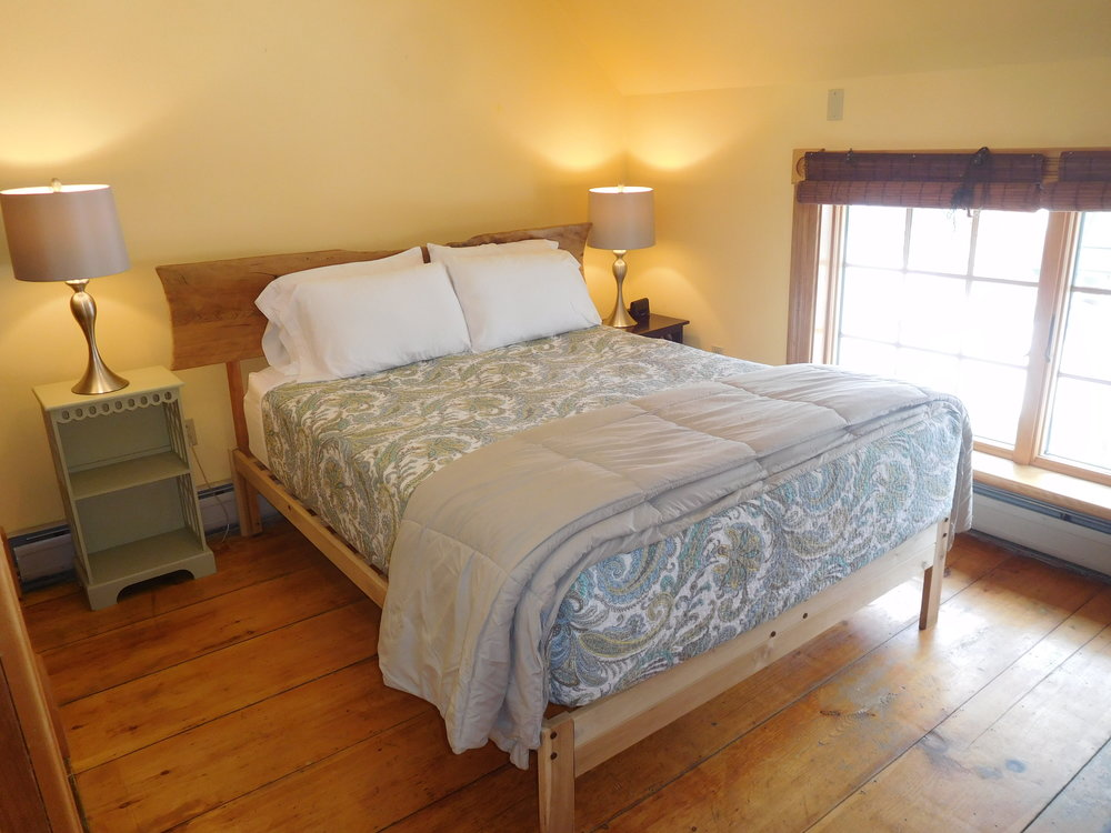 Carriage House downstairs bedroom. Handmade bed, great garden views.