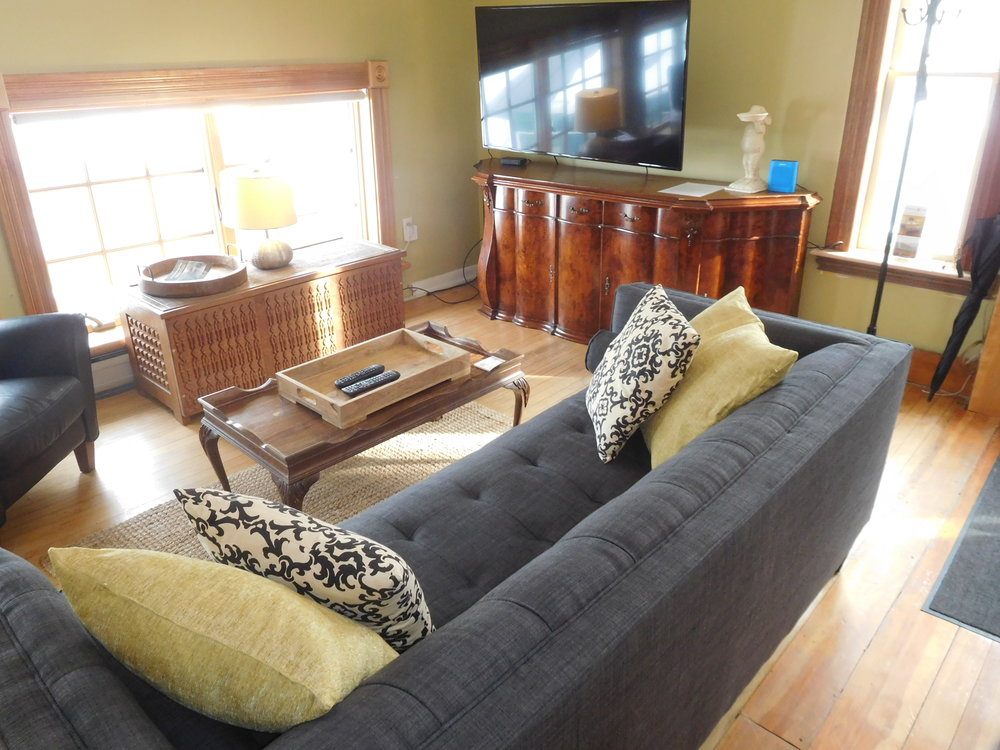 Carriage House living room, comfortable, not fussy. Large screen tv, many cable channels