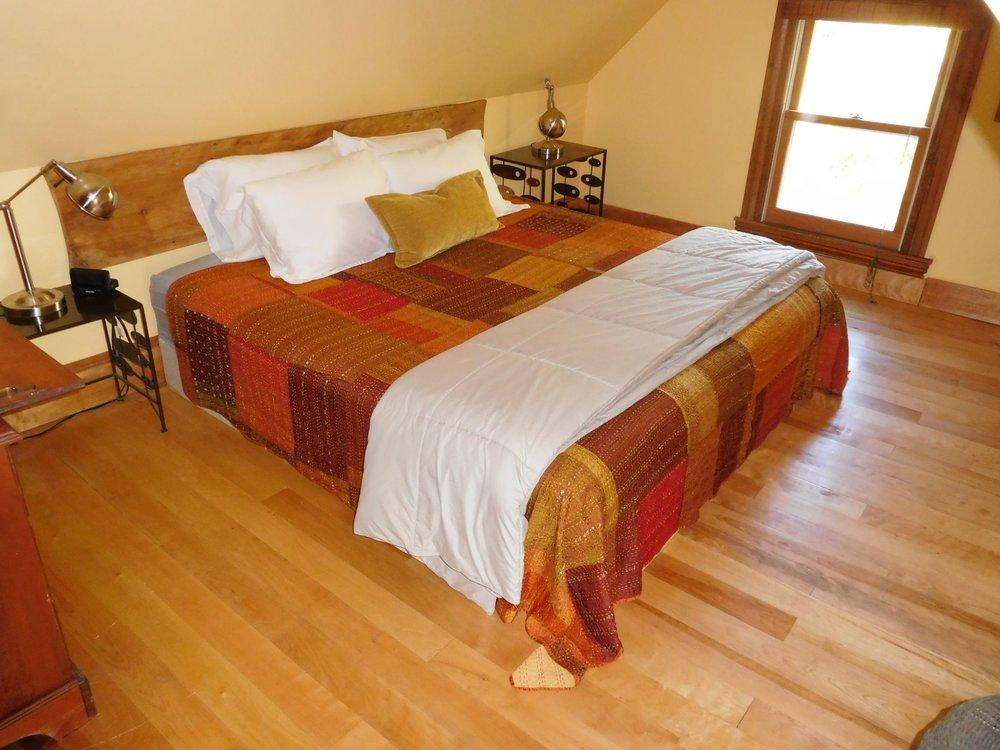 Carriage House upstairs bedroom. Handmade king bed, hardwood floor