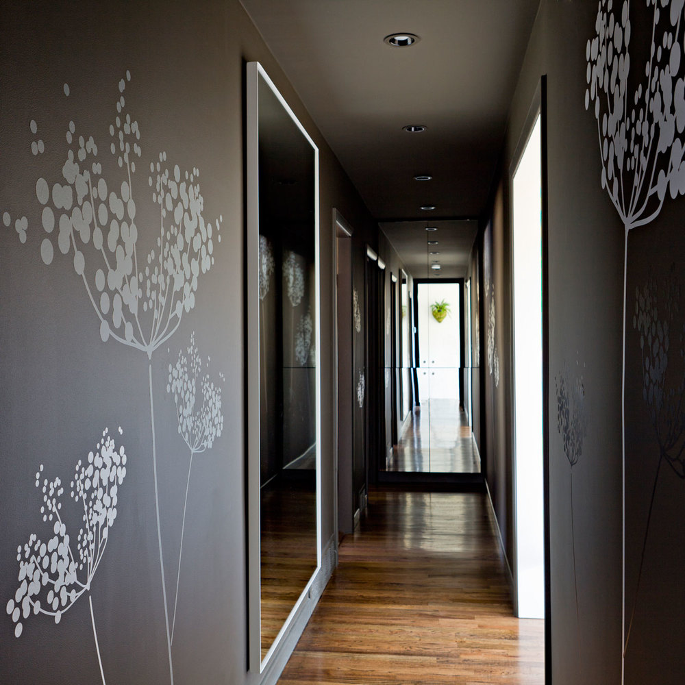 Hall with abstract modern flowers, wall mirror, and mirrored cabinet