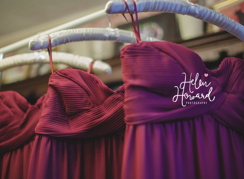 Burgandy bridesmaids dresses on their hangers
