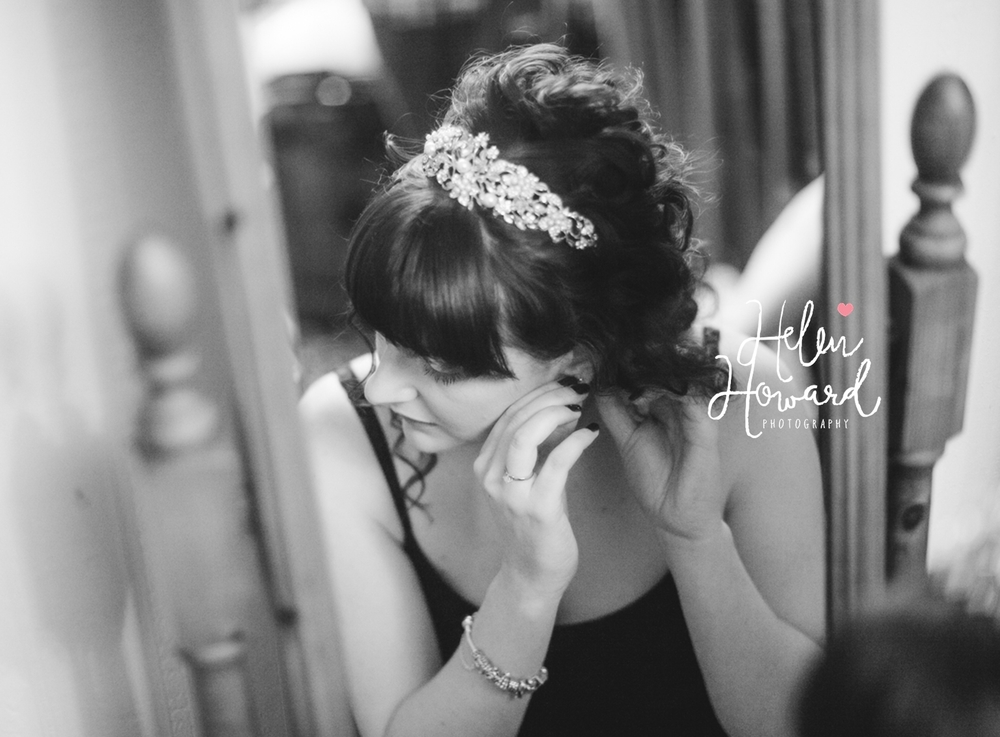 black and white image of a bride putting her earrings on