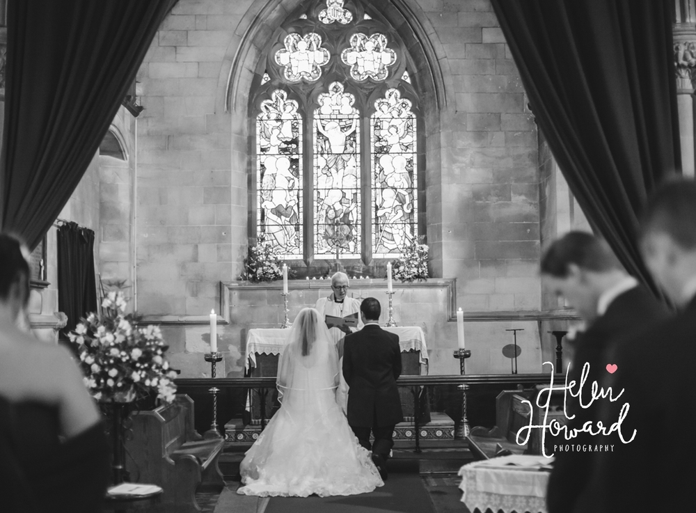 black and white image of a bride and groom kneeling in church