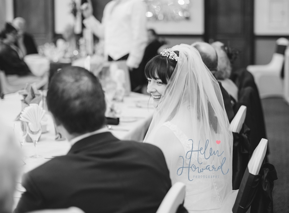 Black and white image of a bride looking at her husband during the speeches
