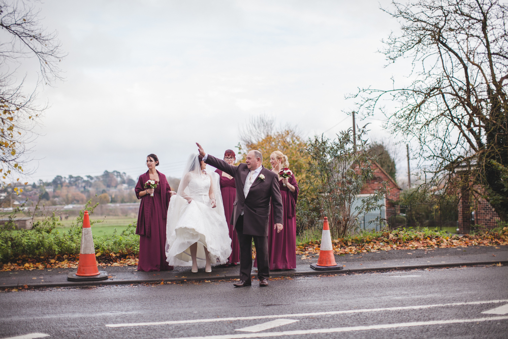 Father stopping the traffic to allow his daughter to cross the road in her wedding dress