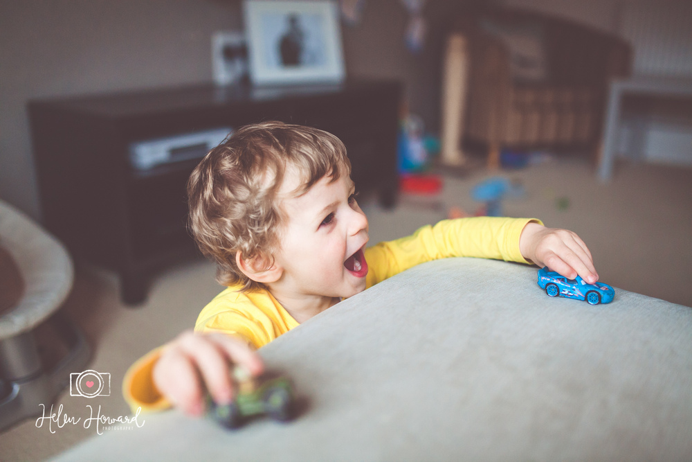 A toddler playing with his toy cars