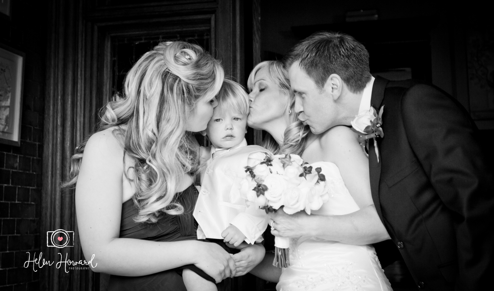 Black and white image of a bride and groom with their children wedding photography at Pendley Manor in Tring