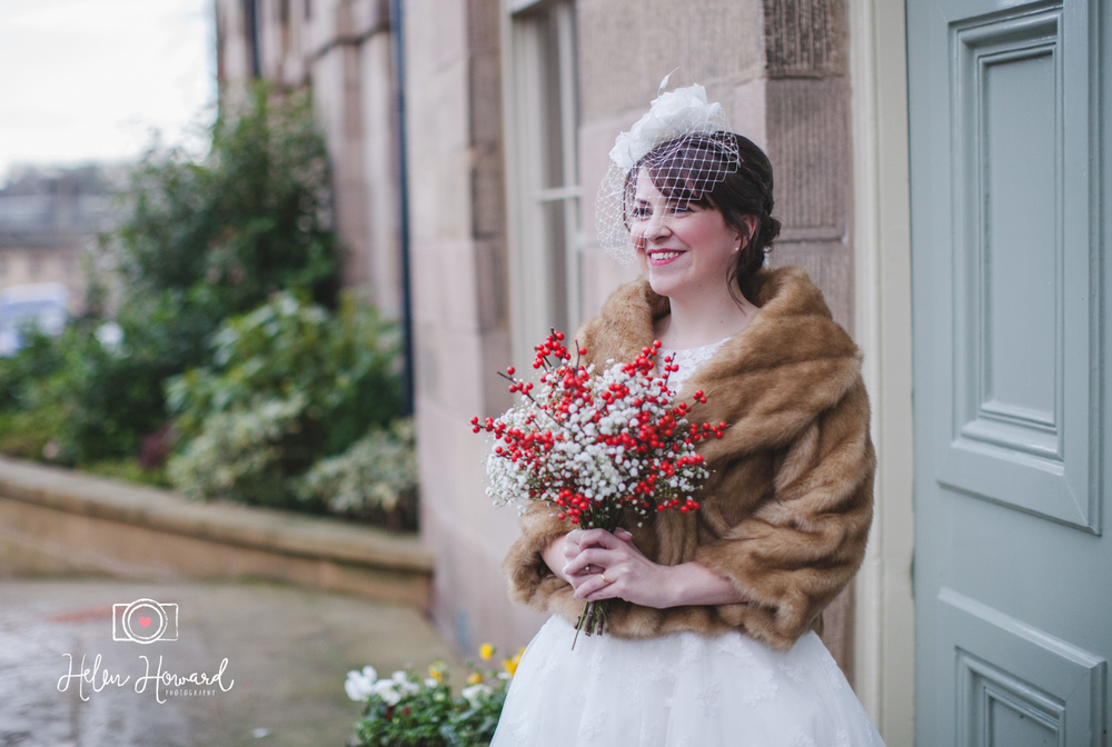 A winter bride with a red berry bouquet wedding photography in Buxton at The Devonshire Dome
