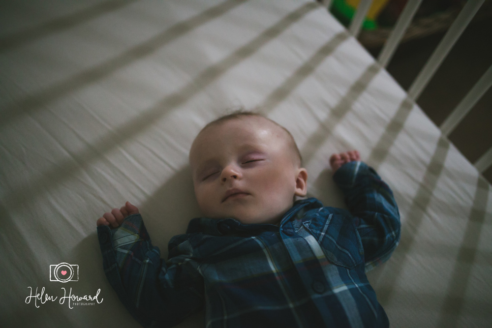 Shadowy image of a baby sleeping in his cot documentary family photography