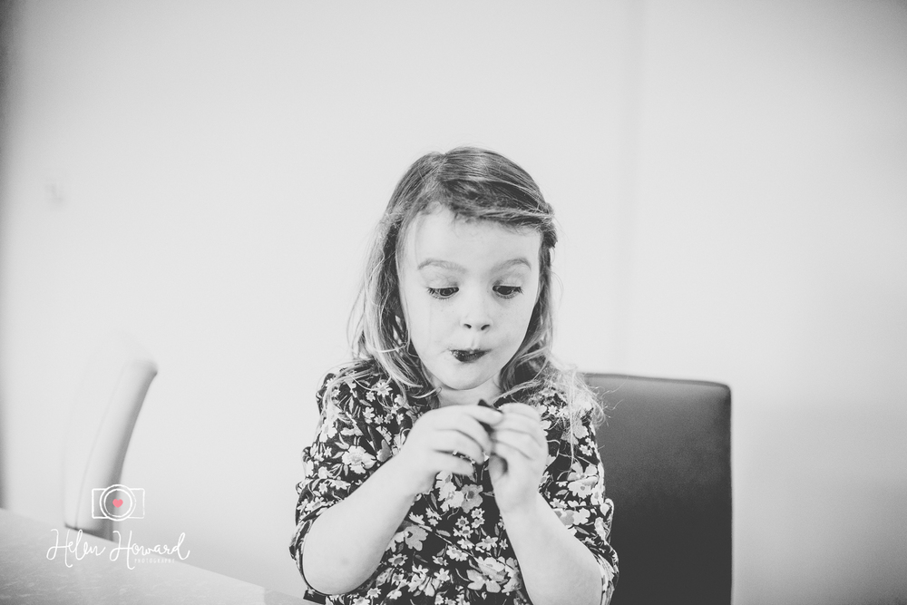 Little girl pulling a funny cute face eating chocolate