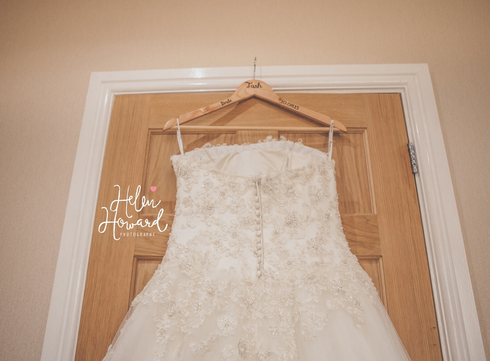 Wedding Dress hanging up during bridal preparation captured by staffordshire wedding photographer Helen Howard