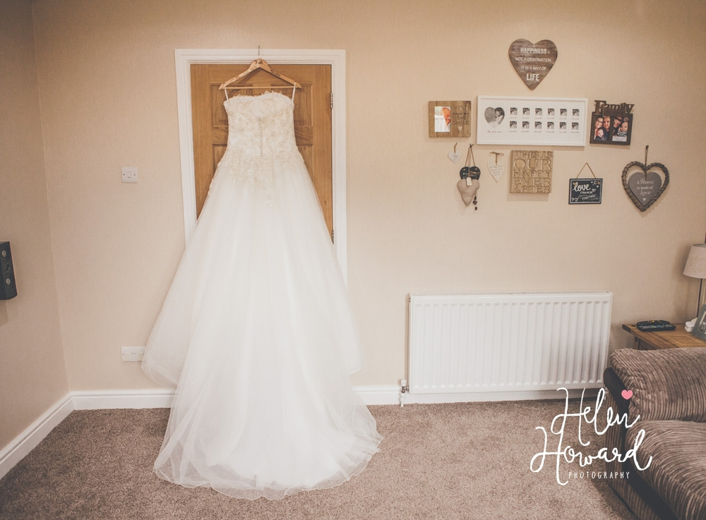 The wedding dress hanging up before a wedding at Shustoke Farm Barns