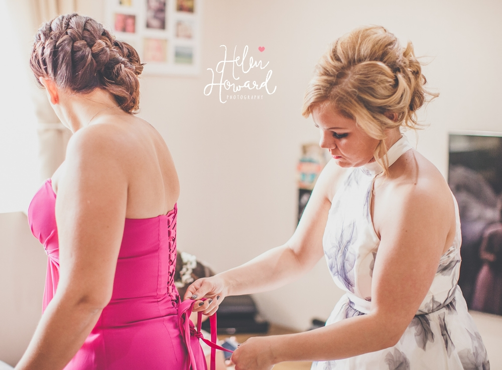 Bridesmaid having her dress laced up