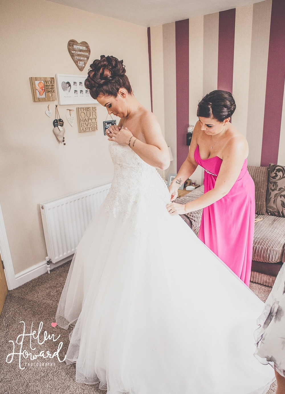 image of a bride putting on her wedding dress