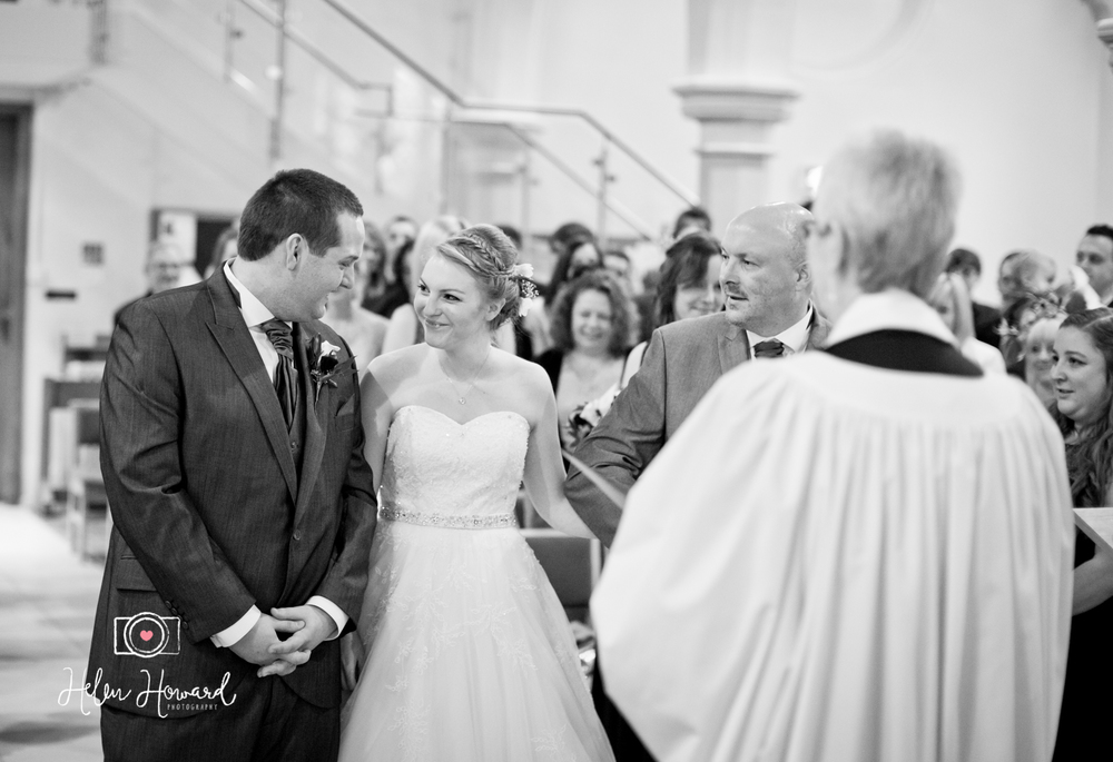 A black and white image taken in the church as a father gives his daughters hand in marriage