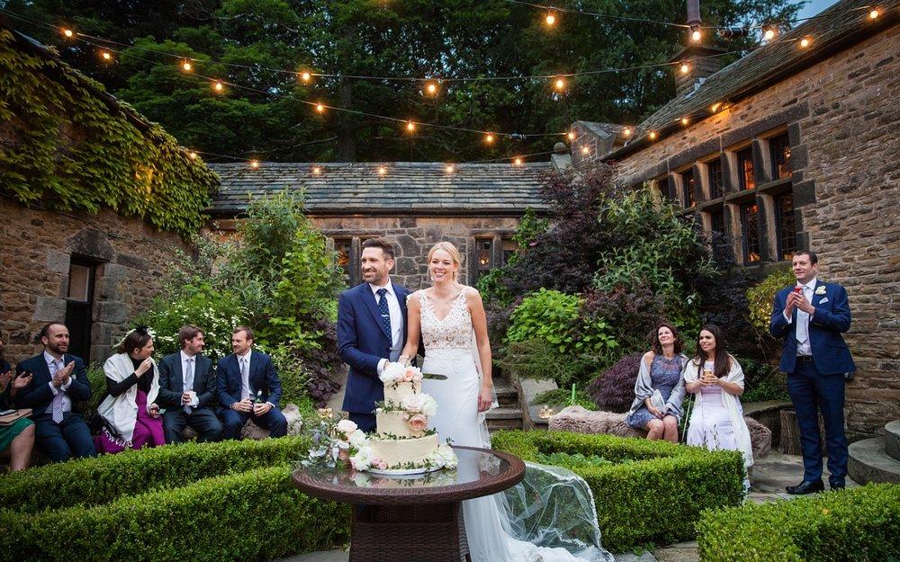Courtyard wedding photographer cake cutting