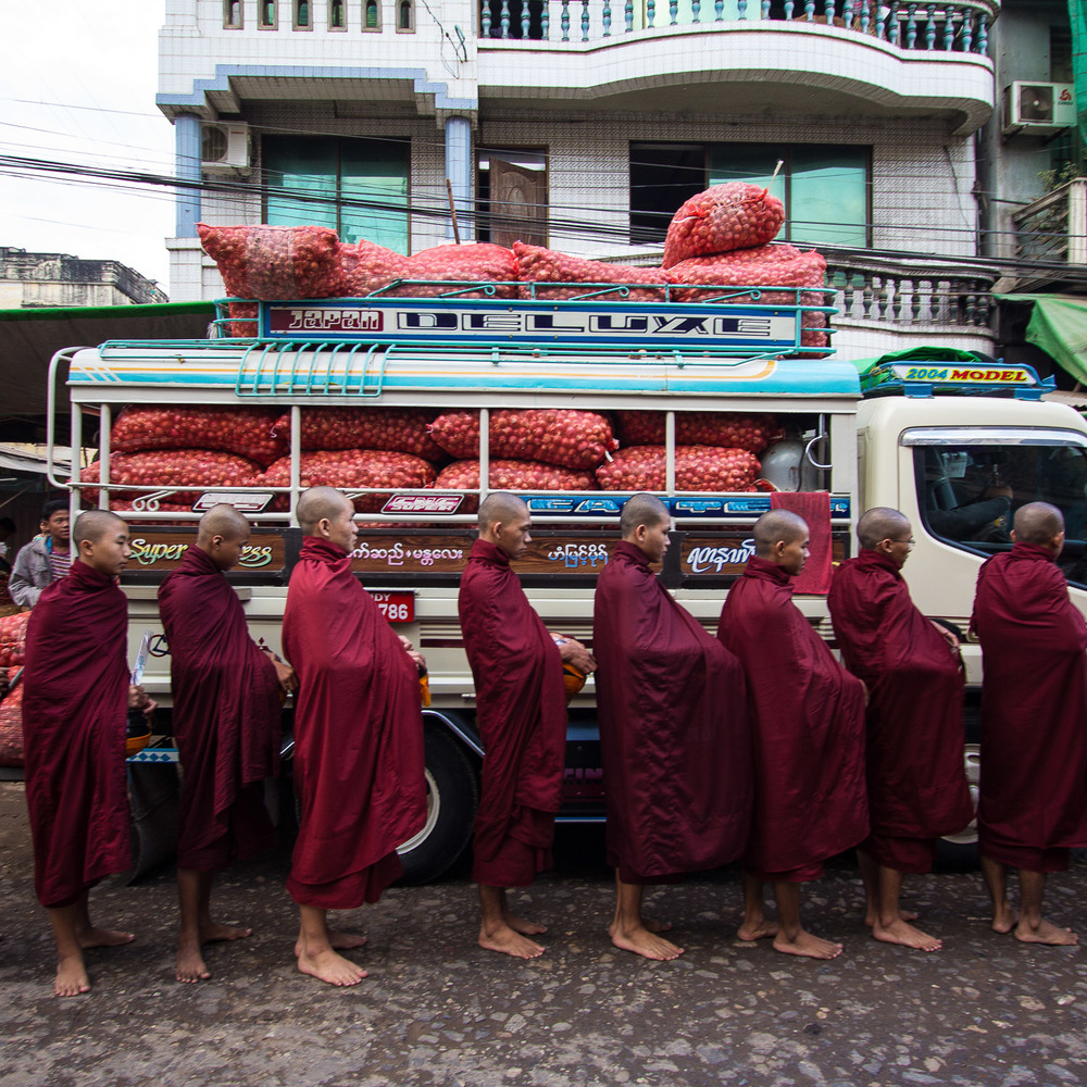 Weird combinations: Monks line up for offerings in front of a truck load of shallots
