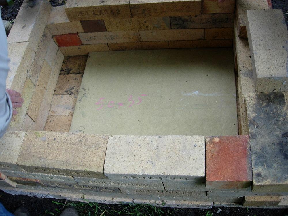 Se ve en el suelo la placa que servirá de separador entre la cámara de combustión y la cámara de cocción. Se ve también a la izquierda que la pared del horno está separada unos 15 cm o así de la placa para que las llamas puedan pasar. A la derecha, se empieza a ver el hueco para la carga de la leña.