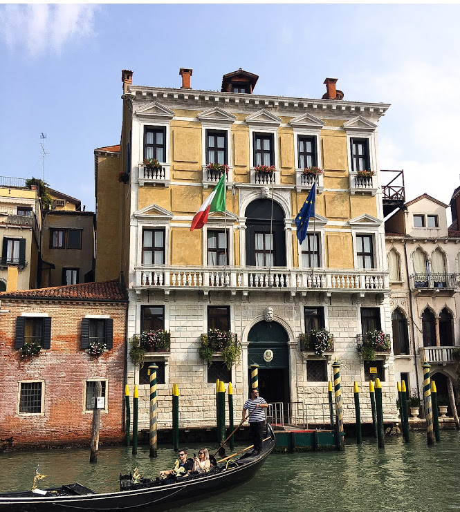 white brick and yellow building on the canal in venice with gondola passing by.JPG