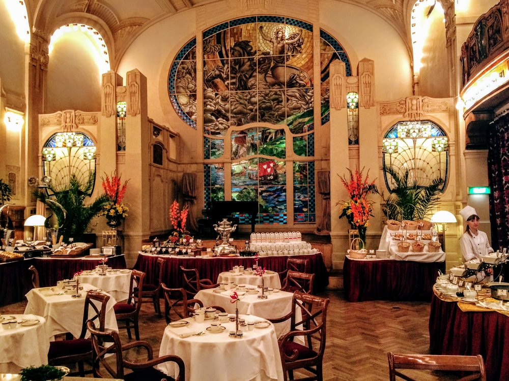 beautiful dining room with stianed glass window behind stage and white table cloths.JPG