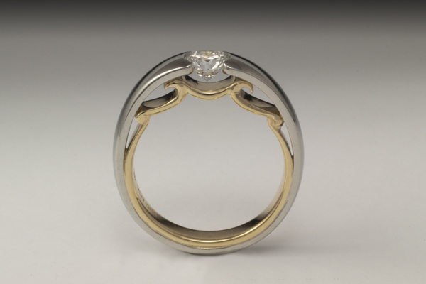 White gold channel set round solitaire with decorative yellow gold interior profile.