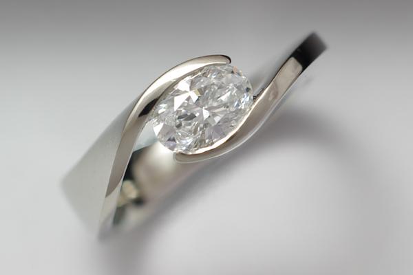 Oval diamond solitaire set in a white gold bypass with a revolved profile.