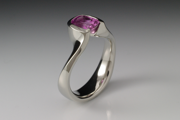 Sculptural white gold band with a cushion cut pink sapphire.