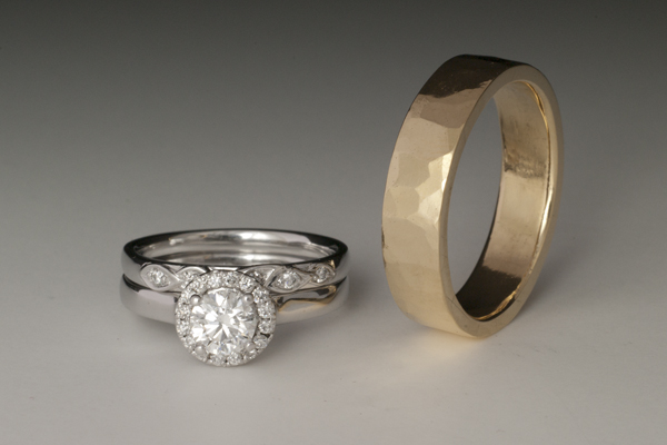 Engagement ring with a prong set center diamond surrounded by a bead set diamond halo.  Ring is paired with a band featuring diamonds set within an infinity design, both in white gold.  Yellow gold men's band with wide hammered pattern.