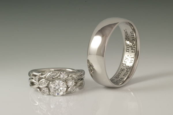 White gold set. Her rings feature accent diamonds set in floral inspired forms twisting around and flanking the center stone.  His ring features inside engraving of a personalized quote.
