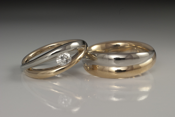 Matching two tone white and yellow gold bands (hers featuring a center diamond) with an interlocking double band apperance.