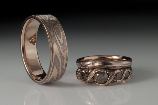 The concept behind the engagement ring was to embrace the recipients affinity for wood jewellery (some of which her partner had made for her).  It is made from Red Gold and Copper Shakudo featuring Chocolate Diamonds.  The couple were so happy with the effect that they had both bands made to match.