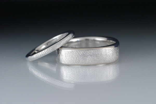 White gold bands.  Each ring features an imprint of the other partner fingerprint.