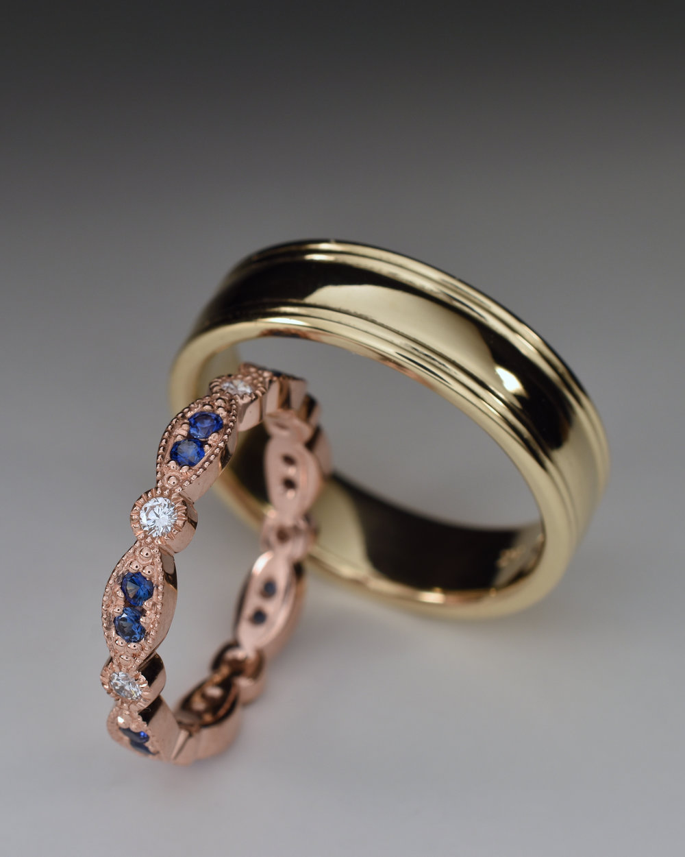 Ladies 14k rose gold band with diamonds and blue sapphires. Gents 14k yellow gold band with linear detail.