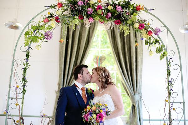 bride-and-groom-under-floral-arch-wedding.jpg