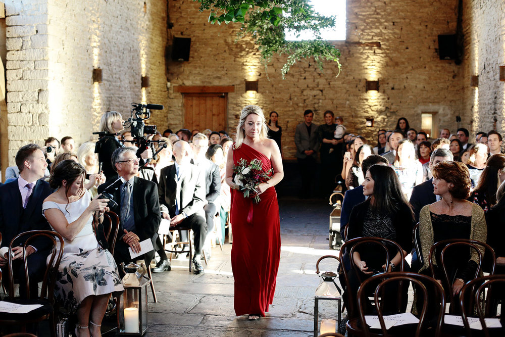 bridesmaid walking down the aisle at Cripps barn Gloucestershire