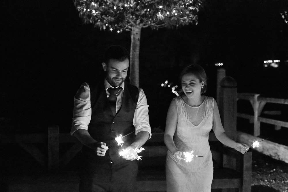 bride and groom with sparklers at cripps barn photo