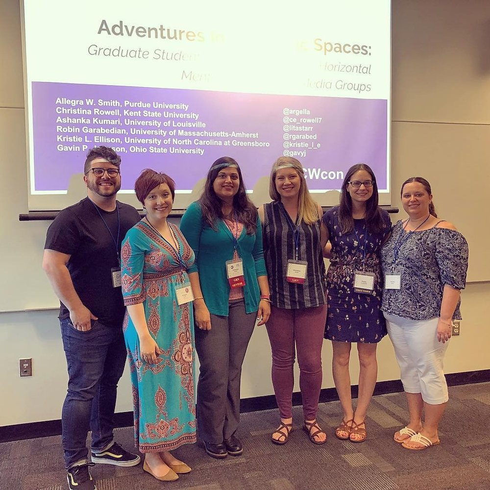 Computers and Writing 2018 - Pictured here (left to right): Gavin P. Johnson, Allegra W. Smith, Ashanka Kumari, Christina Rowell, Robin Garabedian, and Kristie Ellison stand in front of a projector screen displaying their opening slide for their Computers and Writing Roundtable on horizontal mentoring via social media groups.Ellison, Kristie, Robin Garabedian, Gavin Johnson, Ashanka Kumari, Christina Rowell, and Allegra W. Smith.