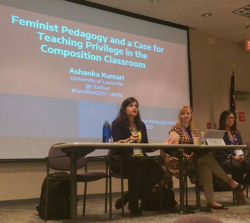 Feminisms and Rhetorics 2017 - Pictured here: Ashanka Kumari presents a paper on approaches to teaching privilege in the writing classroom at the 2017 Feminisms and Rhetorics Conference. She sits at a table on a stage in front of a projector screen displaying the opening slide of her presentation.Kumari, Ashanka.