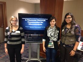"Nodes & Networks Digital Humanities Forum - Pictured here (left to right) Alex Kinnaman, Jennifer Isasi, and Ashanka Kumari pose in front of a television projector of the title slide of the presentation on a methodology for character networks at the macroanalytical level at the Nodes and Networks in the Humanities Digital Humanities Forum.Condello, Morgan, Ross Harrison, Jennifer Isasi, Alex Kinnaman, and Ashanka Kumari. ""A Methodology for Character Networks at the Macroanalytical Level."" Poster. Nodes & Networks in the Humanities: Geometries, Relationships, and Processes – A Digital Humanities Forum. Lawrence, Kansas. September 2014."