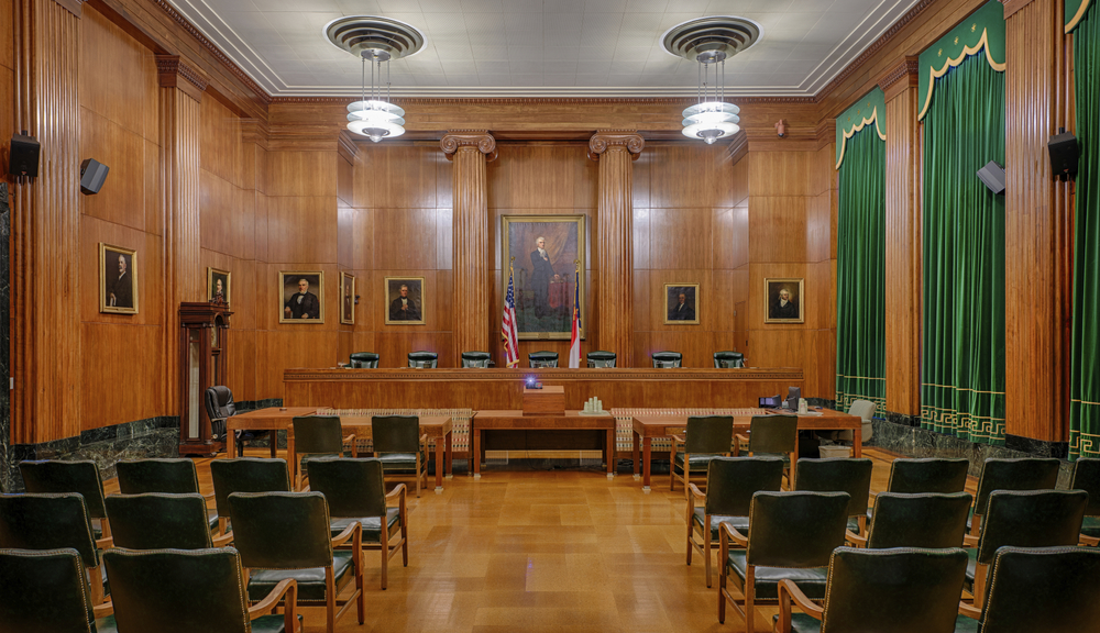 A courtroom with wooden walls and green curtains