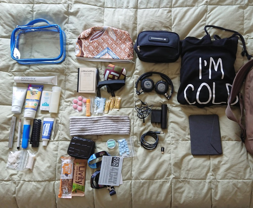 Left column: clear toiletry bag, various face liquids, mascara, eye liner, toothbrush, comb/brush combo, toothpaste. Note the deodorant and cocoa butter stick in bags at the bottom. 2nd column: handmade bag, notebook, eye mask, pepto, chapstick, aleve, ginger, head band, black zip container with vitamins, ear plugs, granola bars 3rd column: case for headphones and cables, headphones, aux cable, usb wall plug, portable battery, usb cable, usb-c adapter Last column: that dang sweater, Kobo e-reader