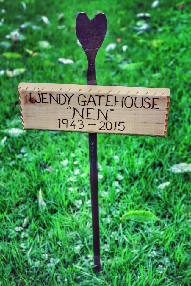 Wooden name-plaque on a hand-forged stake.