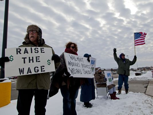 In 2014, numerous protesters stood outside Walmarts and called for higher wages. Image via usatoday.com. (Photo: Darren Hauck, Getty Images)