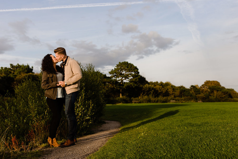 Couple having a kiss on their Wirral Country park pre wedding shoot at sunset