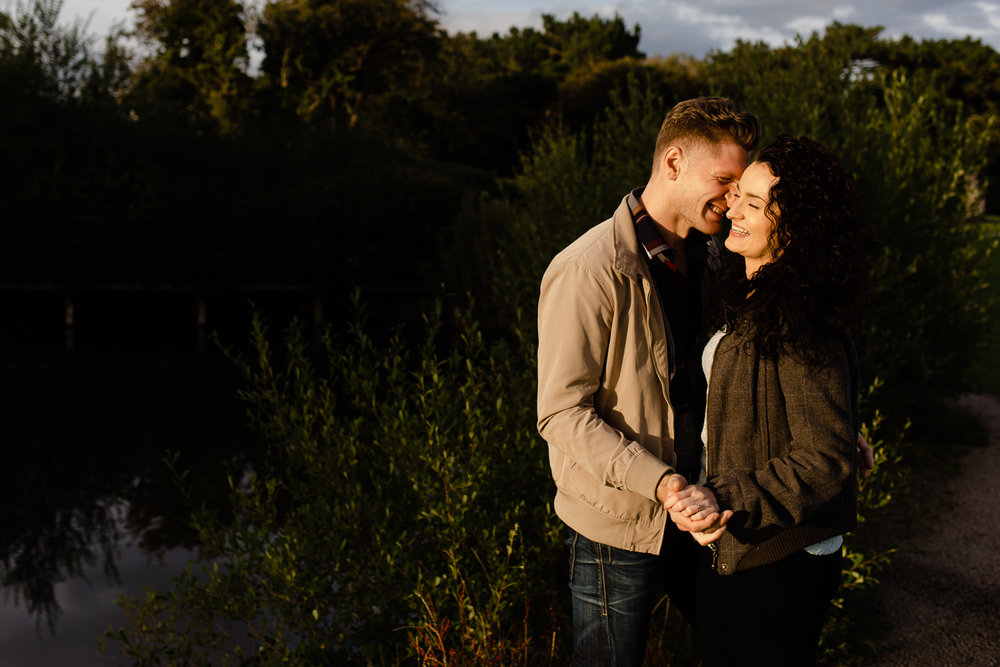 Couple leaning in close and laughing on their pre wedding shoot in Merseyside